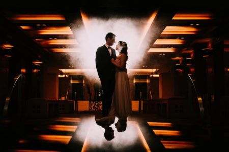 Bride and groom standing in dark orange lit room with smoke behind them - Picture by The Sweet Days