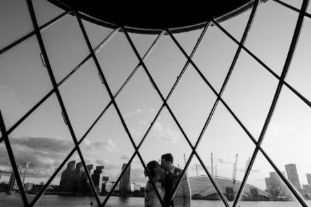 Bride and groom kissing with O2 Arena in background - Picture by Joasis Photography