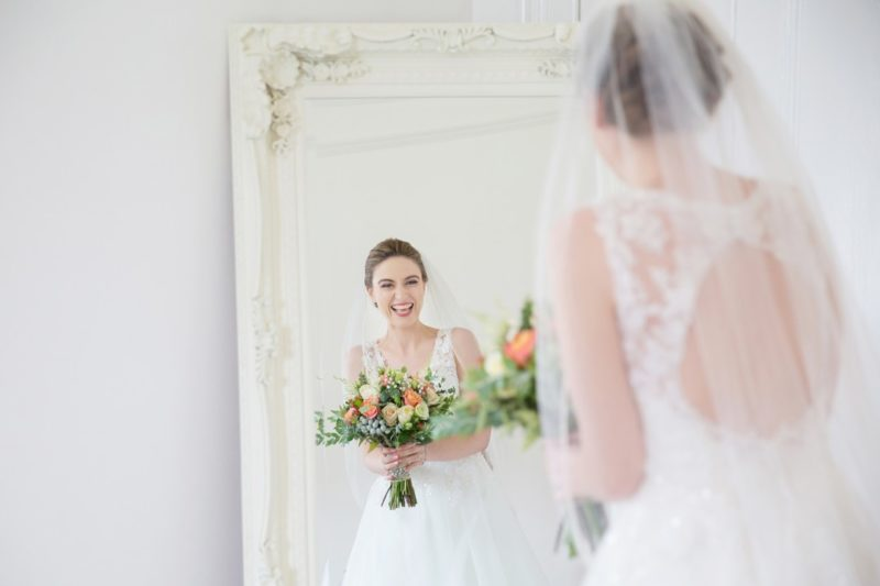 Happy bridre smiling as she looks at her reflection in the mirror - Picture by Helen England Photography