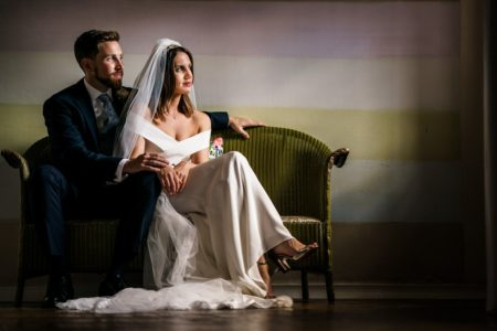 Bride and groom sitting on green chair - Picture by Rob Dodsworth Photography