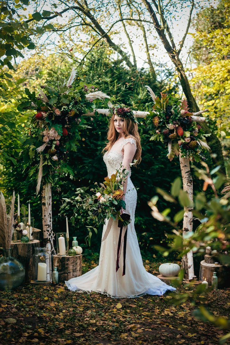 Bride standing in front of ceremony arch in woods