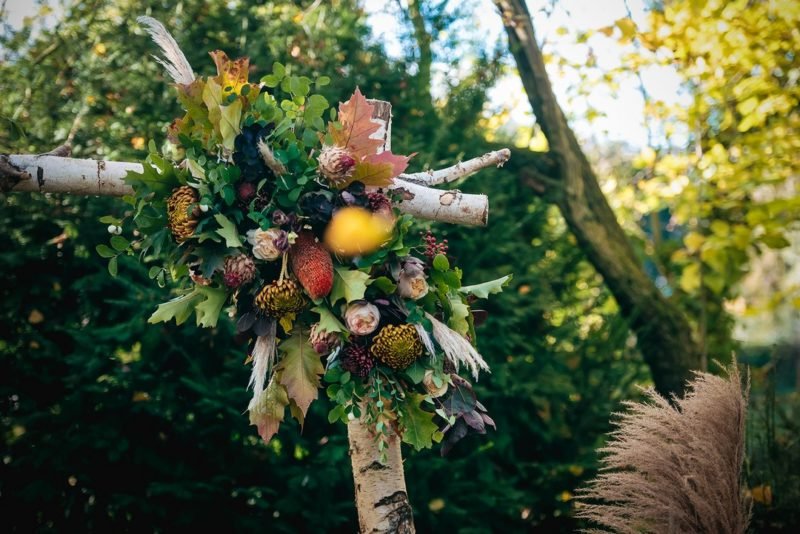 Autumnal flowers and foliage on corner of wedding ceremony arch
