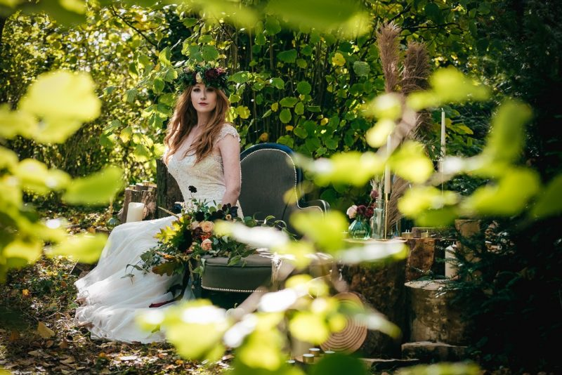 Bride sitting on chez lounge in woods
