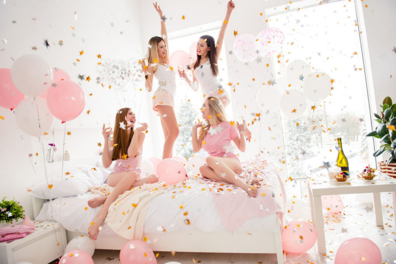 Girls jumping on bed at hen party