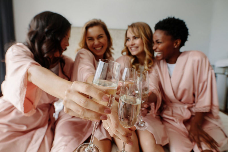 Girls toasting with champagne on bed