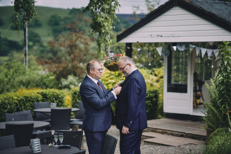 Best man helping groom put on buttonhole