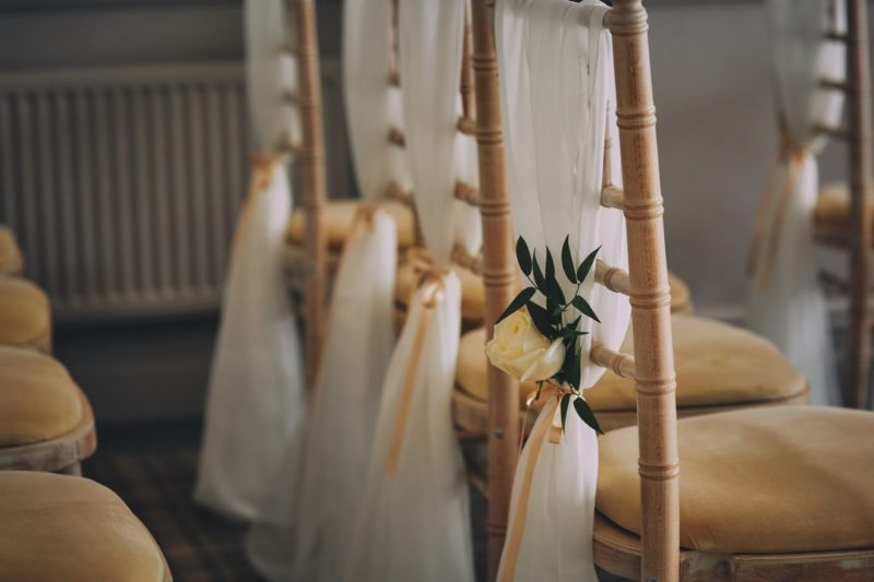Flowers tied to sash on wedding chairs