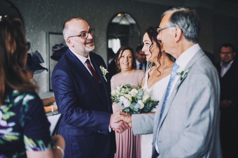 Groom shaking father of the bride's hand