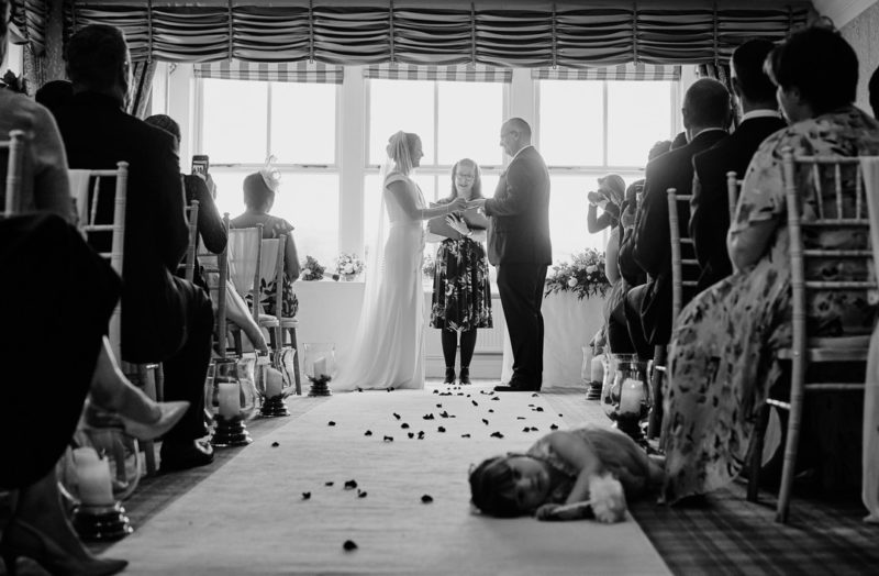 Young girl laying on floor during wedding ceremony
