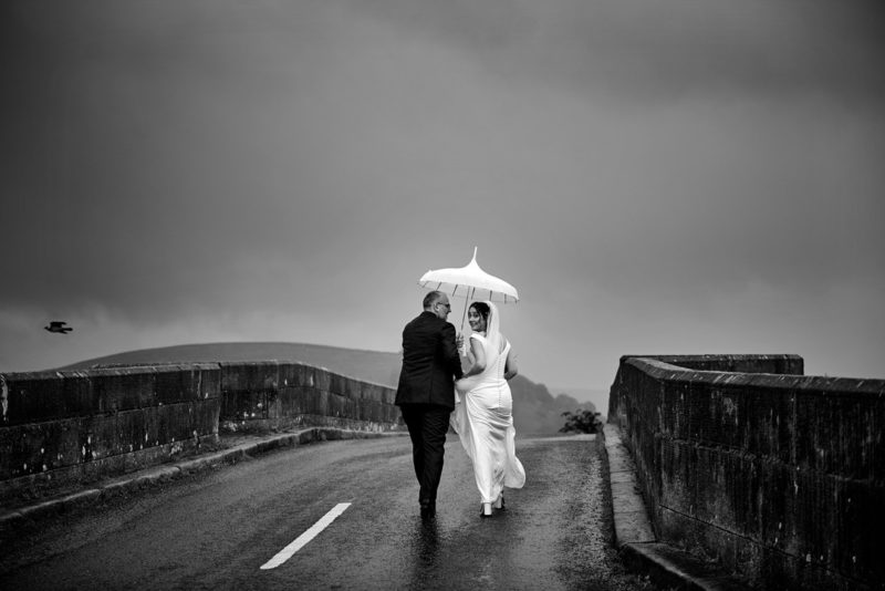 Bride and groom walking over bridge in the rain