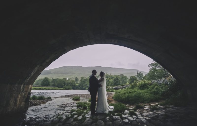 Bride and groom standing under bridge