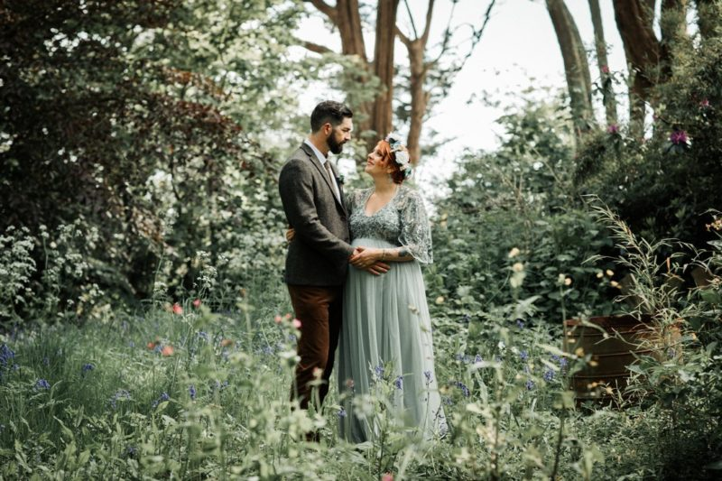 Bride and groom standing amongst greenery in woodland - Picture by Katie Goff Photography