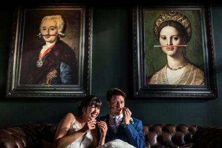 Bride laughing as groom puts pen under his nose like faces in pictures behind them - Picture by Rafe Abrook Photography