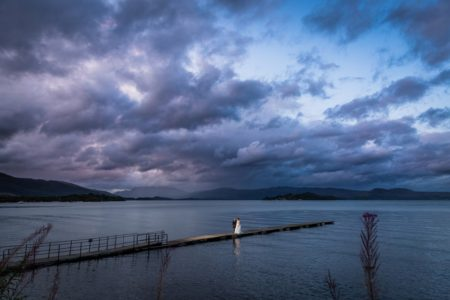 Bride and groom walking across long jetty under cloudy sky - Picture by First Light Photography