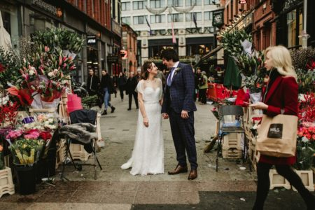 Bride and groom smiling at each other in middle of market flower stall - Picture by Darek Novak Photography