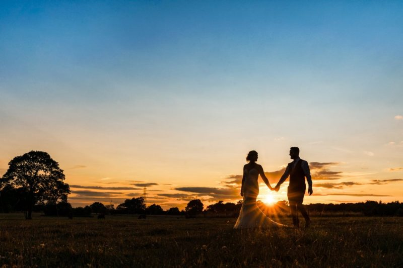 Bride and groom walking holding hands while sun sets between them - Picture by Martin Cheung Photography