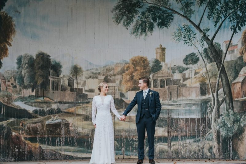 Bride and groom holding hands in front of rustic backdrop - Picture by Matt Fox Photography