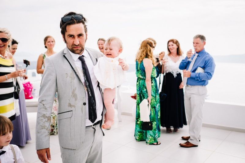 Cross man with comit on him carrying baby out of room at wedding - Picture by Anesta Broad Photography