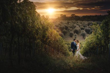 Groom kissing bride on head in beautiful countryside as sun sets - Picture by David West Photography