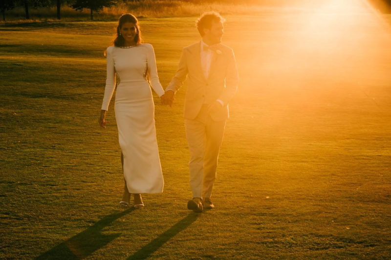 Bride and groom holding hands walking across lawn in hazy sunshine - Picture by Lee Allison Photography