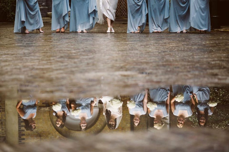 Bride and bridesmaids' legs with reflection of faces in puddle - Picture by Nick Ray Photography