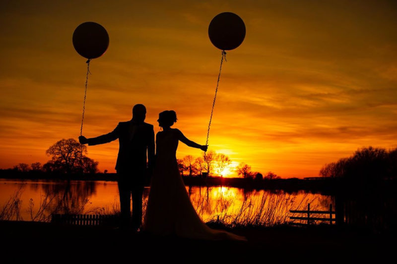 Silhouette of bride and groom holding balloons against sunset - Picture by Carpe Diem Photography