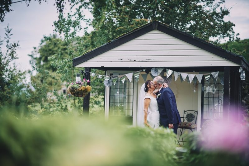Bride and groom kissing by wooden summerhouse