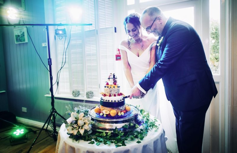 Bride and groom cutting cheese stack cake