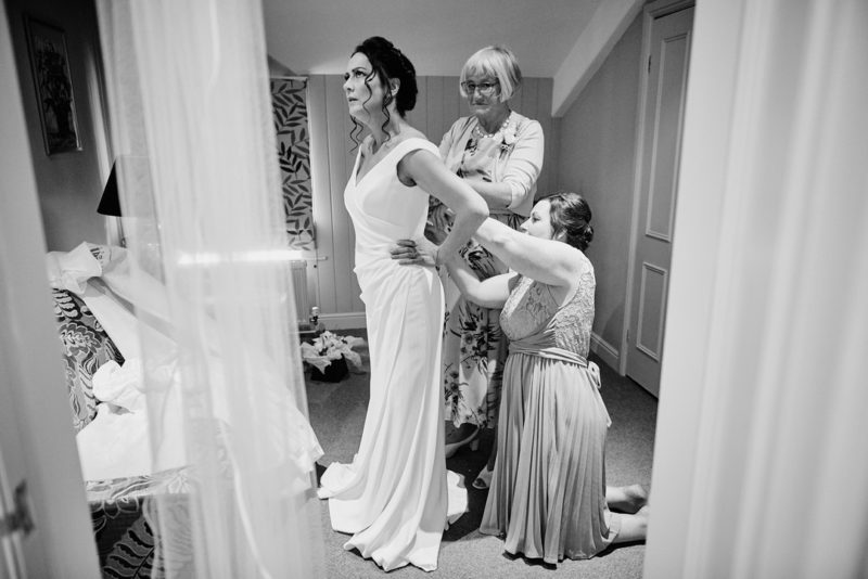 Ladies doing up back of bride's dress