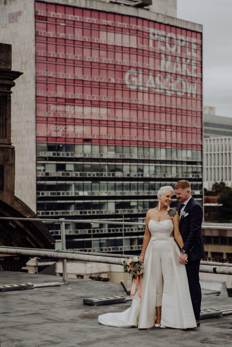 Bride and groom in front of tower block which says People Make Glasgow - Picture by Good Luck Wolf Photography