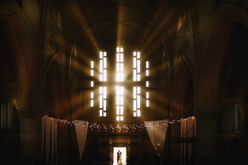 Bride and groomstanding in doorway of church as light shines through windows above them - Picture by Andy Gaines