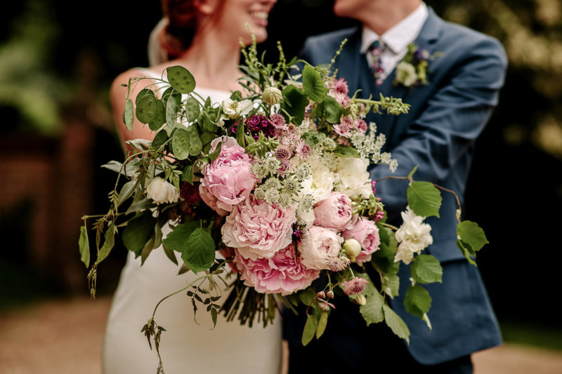 Bride and groom holding oversized wedding bouquet - Picture by Jessy Papasavva Photography