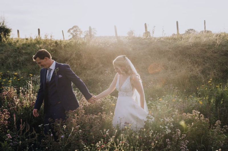 Bride and groom holding hands as they walk through wildflowers - Picture by Clara Cooper Photography