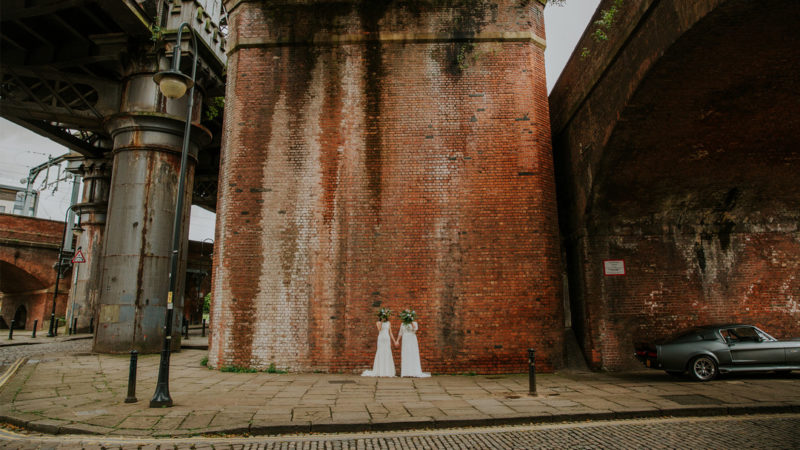 Two brides against wall holding bouquets up their faces - Picture by Maddie Farris Photography