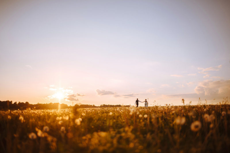 Bride and groom walking across field as sun sets - Picture by Joab Smith