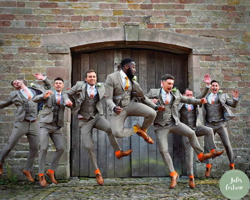 Groomsmen in grey suits and brown shoes jumping in the air - Picture by Jules Fortune Photography