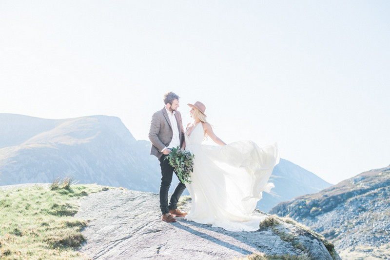 Bride wearing hat with groom on top of mountain - Picture by Laura Jane Photography