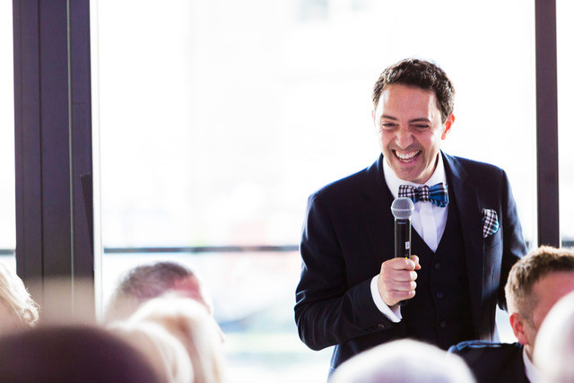 Groom using microphone for wedding speech