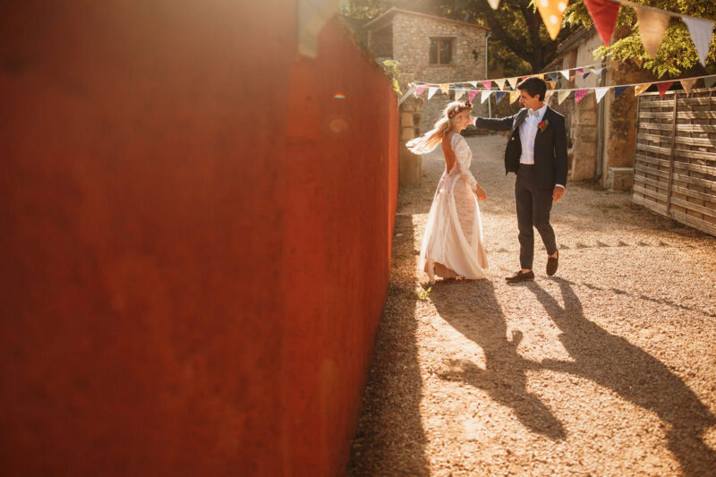 Bride and groom next to wall in sunshine - Picture by Stephen Walker Photography