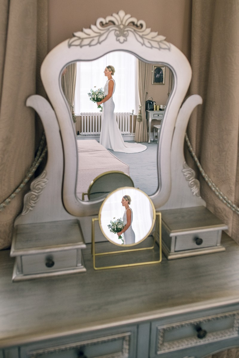 Reflection of bride in two mirrors