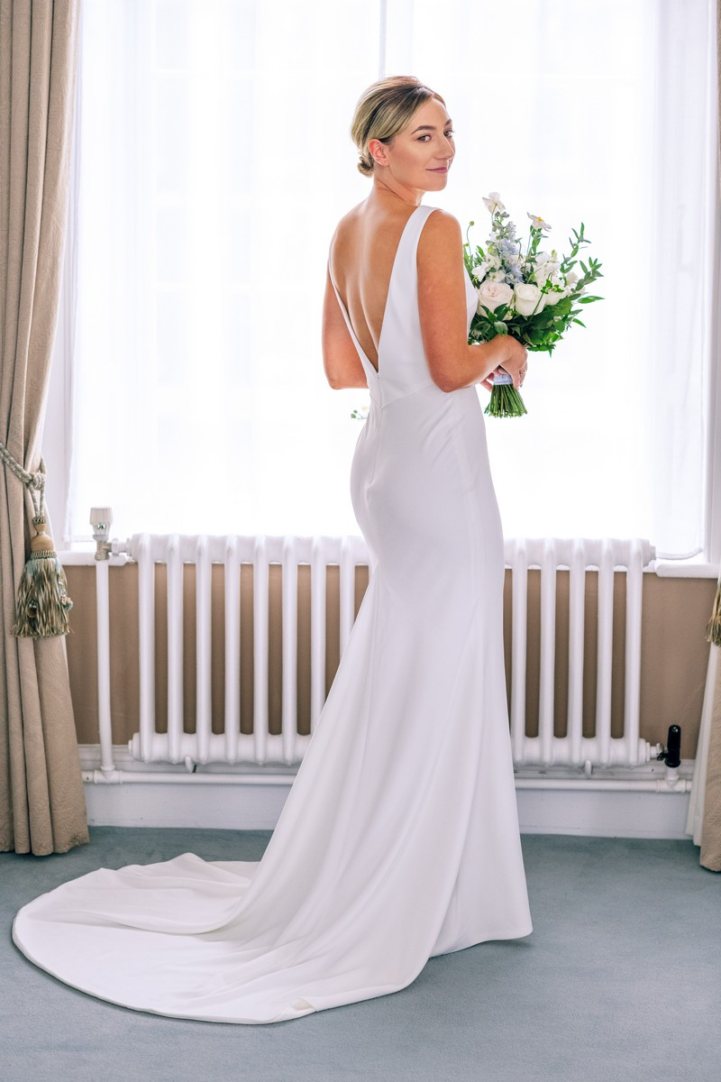 Bride holding bouquet next to window