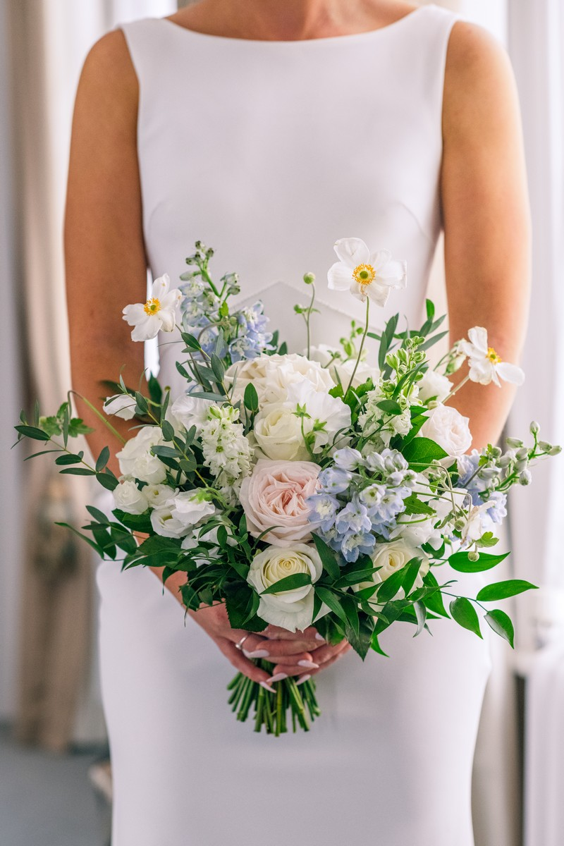 Bridal bouquet with blue, white and pink flowers and green foliage