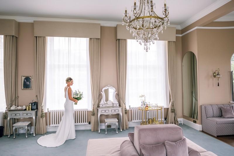 Bride in bedroom at Hawkstone Hall