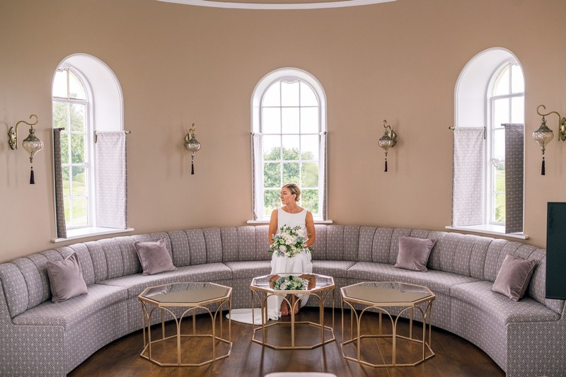 Bride sitting in curved seating area in bedroom at Hawkstone Hall