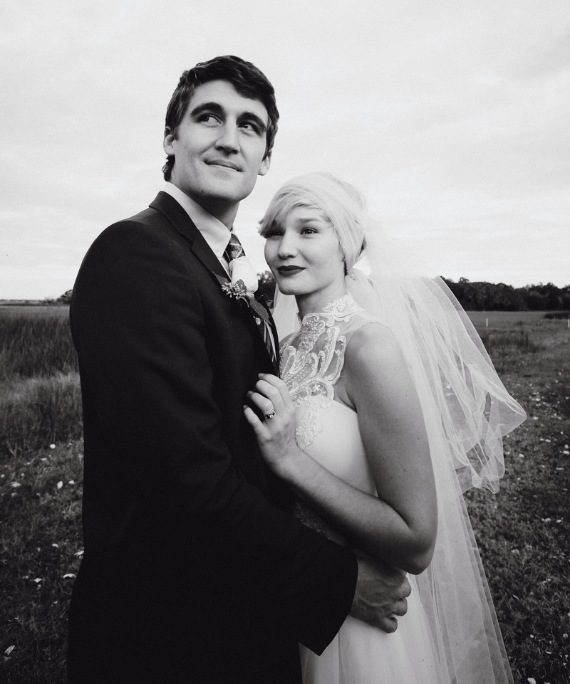1920s style bride with headscarf standing with groom