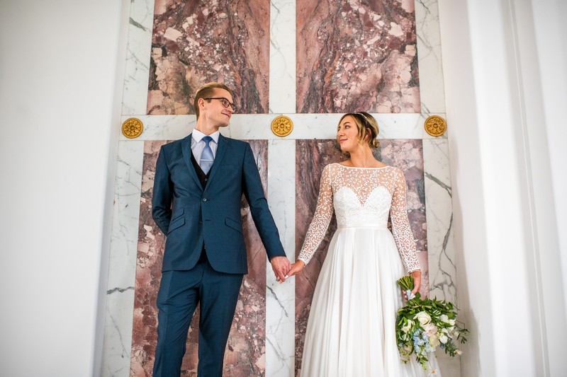 Bride and groom standing in front of marble backdrop