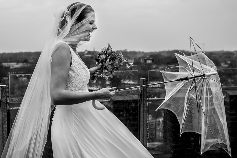 Bride with veil over face laughing at broken umbrella in her hand - Picture by Els Korsten Fotografie