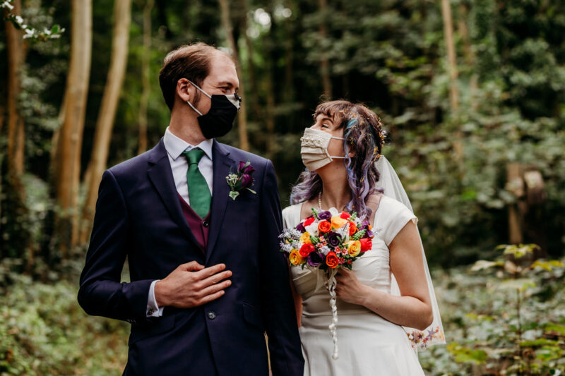 Bride and groom wearing face masks looking at each other - Picture by When Charlie Met Hannah