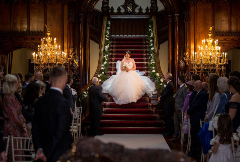 Bride walking down staircase into wedding ceremony - Picture by Peter Rollings Photography