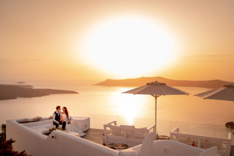 Bride and groom sitting outside venue overlooking sea with big sun in background - Picture by Carpe Diem Photography